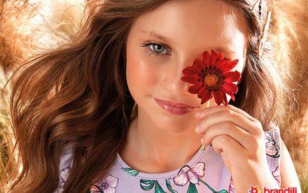 menina segurado uma flor no rosto