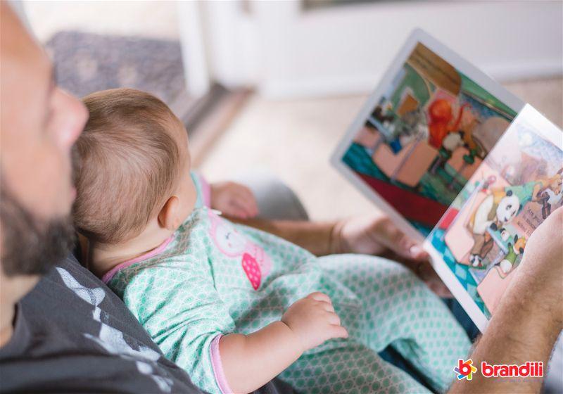 pai lendo livro infantil para bebê