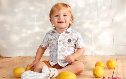 Foto de um bebê menino loiro sentado e sorrindo