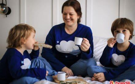 mãe tomando café da manhã na cama com os filhos